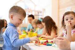 Kinder, die mit buntem Lehm am Kindergarten spielen stockbild