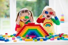 Kinder, die mit bunten Blöcken spielen Stockbilder