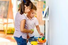 Kinder, die mit bunten Spielwaren am Kindergarten spielen lizenzfreies stockfoto