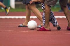 Kinder, die mit dem Ball laufen lizenzfreie stockfotografie