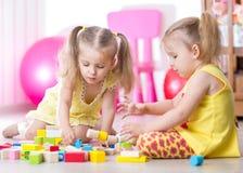 Kinder, die mit den Holzklötzen sitzen auf spielen Stockfotos