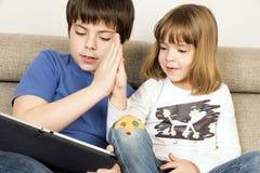 Kinder, die mit einer digitalen Tablette spielen stockfotos
