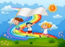Kinder, die mit einer leeren Fahne und einem Regenbogen im Himmel laufen Lizenzfreie Stockfotos