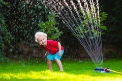 Kinder, die mit Gartenberieselungsanlage spielen stockfotos