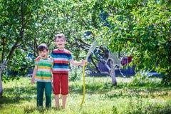 Kinder, die mit Gartenberieselungsanlage spielen Vorsch?lerkinder Lauf und Sprung Wasserspa? des Sommers im Freien im Hinterhof stockfotografie