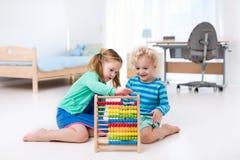 Kinder, die mit hölzernem Abakus spielen Pädagogisches Spielzeug Lizenzfreies Stockbild