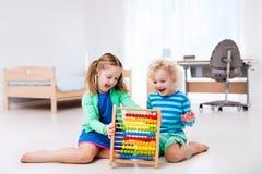 Kinder, die mit hölzernem Abakus spielen Pädagogisches Spielzeug Lizenzfreies Stockfoto