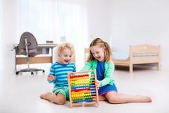 Kinder, die mit hölzernem Abakus spielen Pädagogisches Spielzeug Stockbild