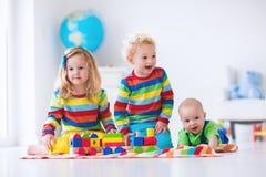 Kinder, die mit hölzernem Spielzeugzug spielen Lizenzfreie Stockbilder