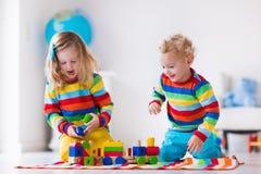 Kinder, die mit hölzernem Spielzeugzug spielen Stockfotos