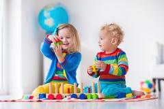 Kinder, die mit hölzernem Spielzeugzug spielen Stockfoto
