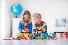 Kinder, die mit hölzernem Spielzeugzug spielen Lizenzfreies Stockfoto