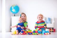 Kinder, die mit hölzernem Spielzeugzug spielen Stockfotografie