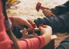 Kinder, die mit h?lzernen Spielwaren auf Boden spielen lizenzfreie stockfotografie