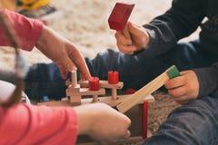 Kinder, die mit h?lzernen Spielwaren auf Boden spielen stockbilder
