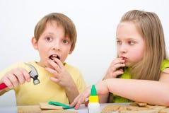 Kinder, die mit Hammer und Nagel arbeiten Stockbilder