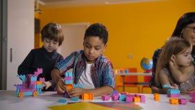 Kinder, die mit hellen konstruierenden Ziegelsteinen errichten stock footage