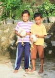 Kinder, die mit Hennen spielen Stockbild