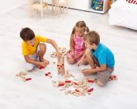 Kinder, die mit hölzernen Blöcken spielen Lizenzfreie Stockfotos
