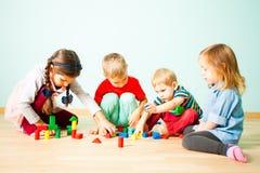 Kinder, die mit Holzklötzen am Kindergarten spielen stockfotografie