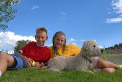Kinder, die mit Hund sich entspannen Lizenzfreie Stockfotografie