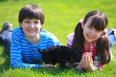 Kinder, die mit Hund spielen Lizenzfreie Stockfotos