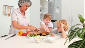 Kinder, die mit ihrer Großmutter kochen stock video