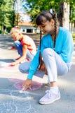 Kinder, die mit Kreide zeichnen stockbild