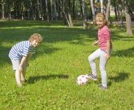 Kinder, die mit Kugel spielen Stockfotos