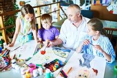 Kinder, die mit Lehrer in der Kunstkategorie malen Lizenzfreies Stockfoto