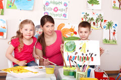 Kinder, die mit Lehrer in der Kunstkategorie malen. lizenzfreies stockfoto