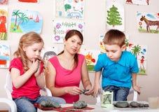 Kinder, die mit Lehrer vom Lehm spielen. Lizenzfreie Stockfotografie