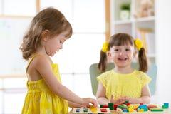 Kinder, die mit logischem Spielzeug auf Schreibtisch im Kindertagesstättenraum oder -kindergarten spielen Kinder, die Formen, Far lizenzfreie stockbilder