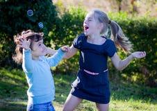 Kinder, die mit Luftblasen spielen Stockfotografie