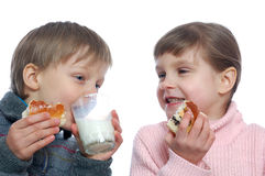 Kinder, die mit Milch zu Mittag essen Stockbilder