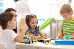 Kinder, die mit pädagogischen Spielwaren im Kindergarten spielen Kindergärtnerin, die um Kinder sich kümmert stockbilder
