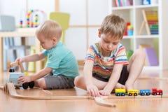 Kinder, die mit pädagogischen Spielwaren und errichtender Eisenbahn spielen lizenzfreies stockbild