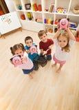Kinder, die mit piggybanks spielen Stockbild