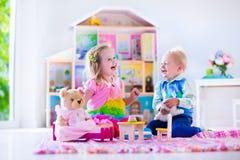 Kinder, die mit Plüschtieren und Puppenhaus spielen Stockbild