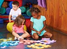 Kinder, die mit Puzzlen im Kindergarten spielen lizenzfreie stockfotografie