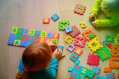Kinder, die mit Puzzlespiel, Zahlen und Formen lernend spielen Stockfotografie