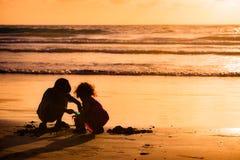 Kinder, die mit Sand durch das Meer bei Sonnenuntergang in Tobago spielen lizenzfreies stockbild