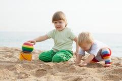 Kinder, die mit Sand in Meer spielen Lizenzfreies Stockbild