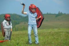 Kinder, die mit Schild kämpfen Lizenzfreies Stockbild
