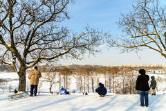 Kinder, die mit Schnee nach Schneefällen am Winter-Tag in Tineretului-Park von Bukarest spielen Stockbild