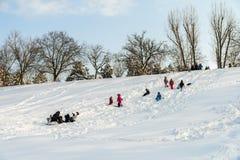 Kinder, die mit Schnee nach Schneefällen am Winter-Tag in Tineretului-Park von Bukarest spielen Stockfotografie