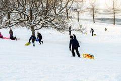 Kinder, die mit Schnee nach Schneefällen am Winter-Tag in Tineretului-Park von Bukarest spielen Lizenzfreie Stockbilder