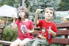 Kinder, die mit Seifenballonen spielen Lizenzfreie Stockfotografie