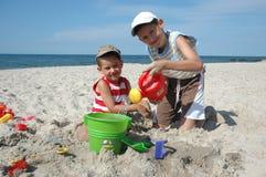 Kinder, die mit Spielwaren auf dem Strand spielen Stockbilder