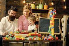 Kinder, die mit Spielwaren spielen Reizende Familie im Spielzimmer Mutter und Kind, die mit Autos auf Rennstrecke aus Plastikblöc Stockbild